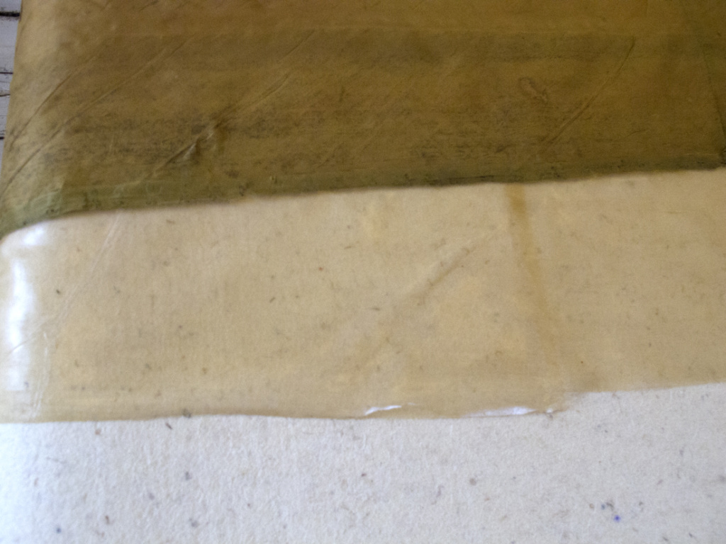 Fanen lamineres med imprægneret silkegaze, der her ses under den ene silkedug.