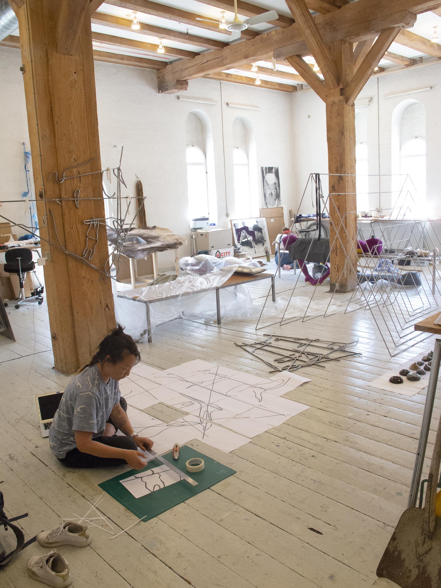 Annesofie Sandal arbejder på lysekronestruktur i atelieret