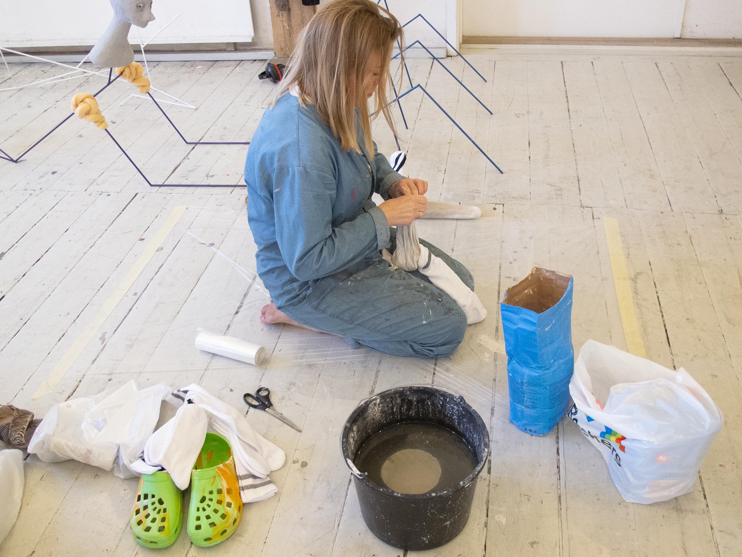 Nanna Starck støber gips i tennissokker i atelieret